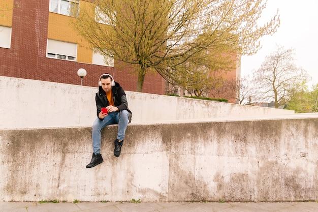 Beau jeune homme utilisant son téléphone portable assis sur un mur de la ville, avec beaucoup d'espace de copie. concept de vie de rue