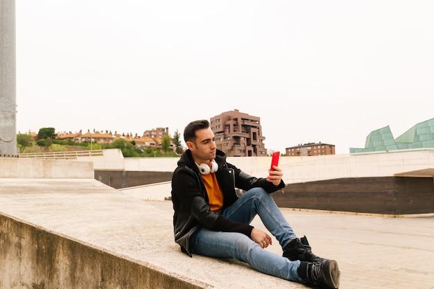 Beau jeune homme utilisant son téléphone portable dans la rue pour communiquer avec ses amis via les médias sociaux et internet haut débit