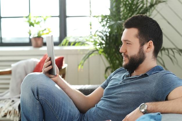 Beau jeune homme utilisant une tablette numérique ou un ebook