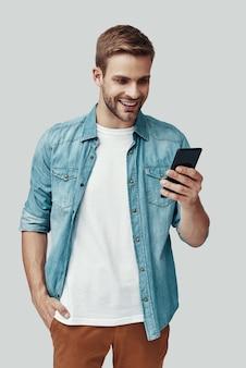 Beau jeune homme utilisant un téléphone intelligent et souriant en se tenant debout sur fond gris