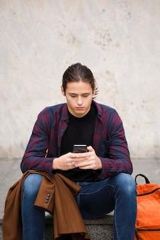 Beau jeune homme vérifiant son téléphone