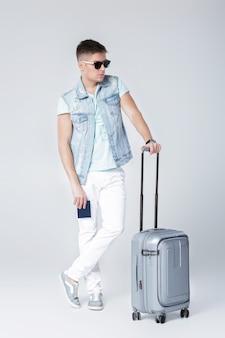 Beau jeune homme en veste en jean avec valise et avec passeport
