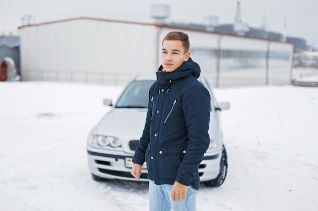 Beau jeune homme en vêtements chauds posant sur le fond des voitures