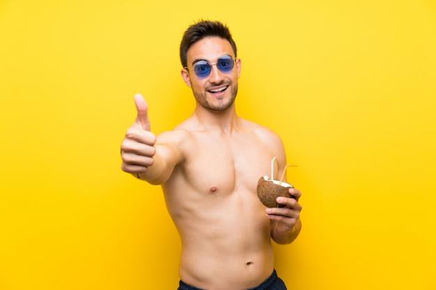 Beau jeune homme en vêtements d'été avec le pouce levé parce que quelque chose de bien est arrivé
