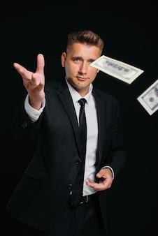 Un beau jeune homme vêtu d'un élégant costume noir jette des dollars d'argent sur fond noir. un homme d'affaires élégant. un grand homme d'affaires.