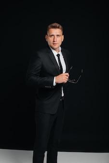 Un beau jeune homme vêtu d'un élégant costume noir pose sur fond noir. un homme d'affaires élégant. un grand homme d'affaires.