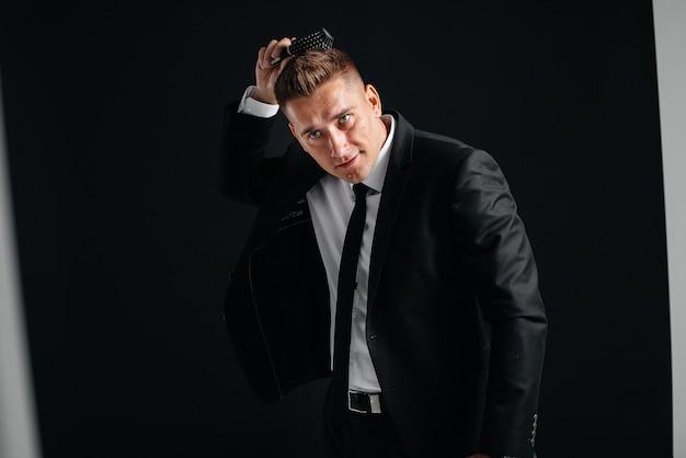 Un beau jeune homme vêtu d'un élégant costume noir se peigne les cheveux et sourit sur fond noir. nettoyer, préparer.