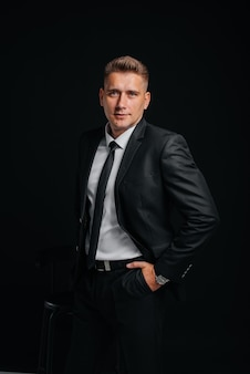 Un beau jeune homme vêtu d'un élégant costume noir et souriant sur fond noir. nettoyer, préparer.