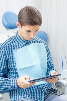 Beau jeune homme en visite au cabinet dentaire. il est assis sur la chaise, tient une tablette dans les mains et attend le dentiste. dentisterie