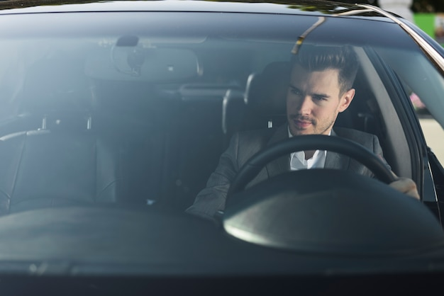 Beau jeune homme voyageant dans une voiture de luxe