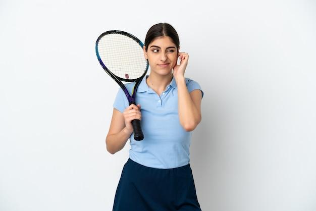Beau jeune joueur de tennis femme caucasienne isolée sur fond blanc frustré et couvrant les oreilles