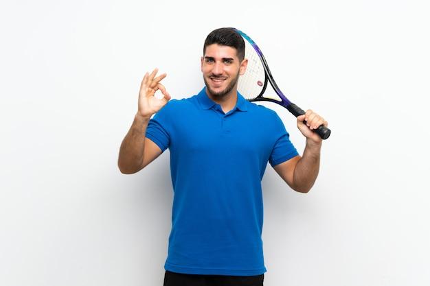 Beau jeune joueur de tennis homme sur mur blanc isolé, montrant un signe ok avec les doigts
