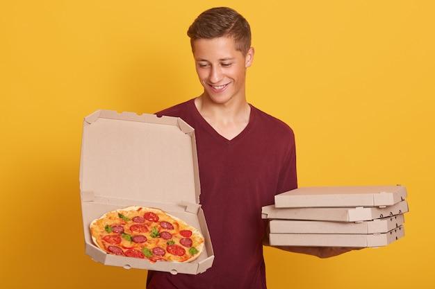 Beau jeune livreur habille un t-shirt décontracté bordeaux tenant une pizza dans des boîtes