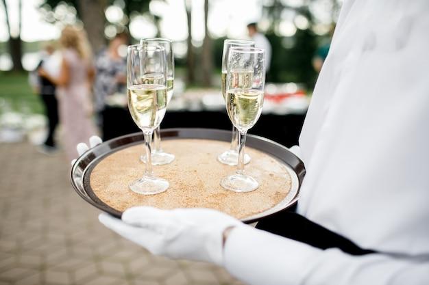 Beau jeune majordome tenant un plateau en argent avec deux verres de champagne