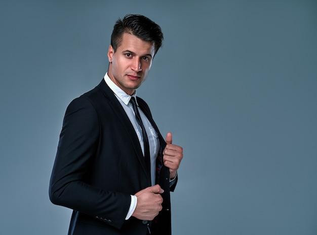 Beau jeune mannequin brune, vêtu d'un costume noir et blanc, regardant avec attitude, posant en studio, isolé sur fond gris. portrait d'homme d'affaires. espace de copie. vue horizontale.
