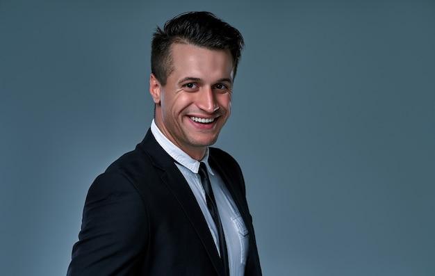 Beau jeune mannequin brune, vêtu d'un costume noir et blanc, souriant, posant au studio, isolé sur fond gris. portrait d'homme d'affaires. espace de copie. vue horizontale.