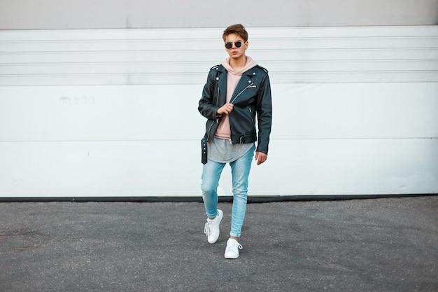 Beau jeune mannequin d'un homme avec des lunettes de soleil dans une veste en cuir noir, un sweat-shirt rose, un jean bleu et des baskets blanches près d'une porte blanche en métal
