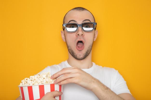 Beau jeune mec dans des lunettes 3d et avec du pop-corn. mur jaune