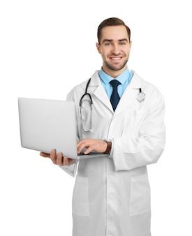 Beau jeune médecin avec ordinateur portable sur blanc