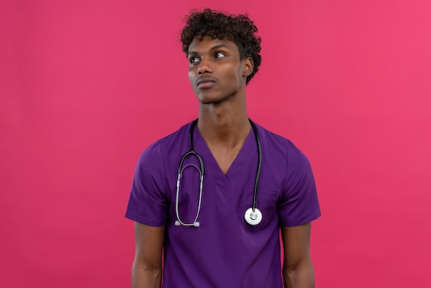 Un beau jeune médecin à la peau sombre avec des cheveux bouclés portant l'uniforme violet avec stéthoscope à côté