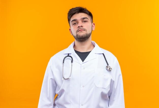 Beau jeune médecin portant une robe médicale blanche, des gants médicaux blancs et un stéthoscope à sérieusement debout sur un mur orange