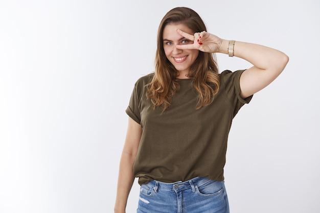 Beau jeune modèle féminin séduisant sensuel et confiant posant un jean t-shirt olive sur fond blanc, souriant joyeusement insouciant, montrant un geste de victoire chanceux de paix, signe disco près de l'œil