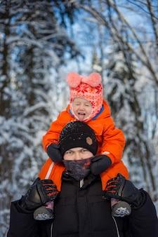 Beau jeune papa et sa petite fille mignonne s'amusent en plein air en hiver.