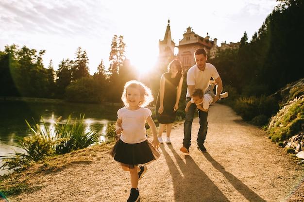 Beau jeune père et belle mère dans la nature d'été ensoleillée jouant avec leurs petits enfants mignons