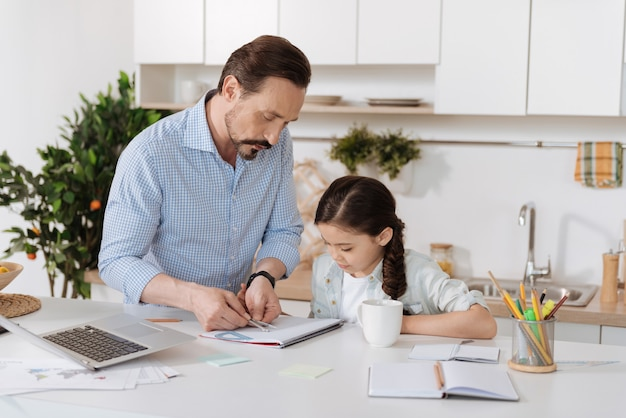 Beau jeune père debout derrière le comptoir de la cuisine et montrant à sa fille comment mesurer la distance avec une paire de boussoles alors qu'elle regarde attentivement