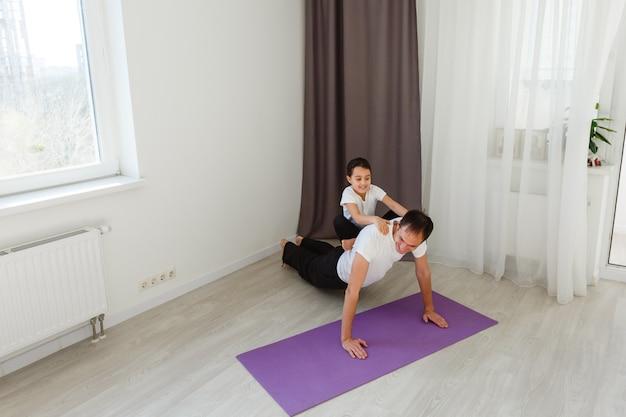 Beau jeune père et sa mignonne petite fille font du commerce de planche avec une jambe levée sur le sol à la maison. entraînement de fitness en famille.