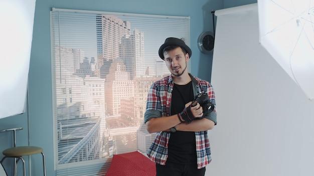 Beau jeune photographe au chapeau tenant la caméra et souriant dans une séance photo studio moderne