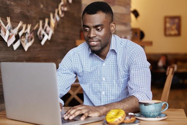 Beau jeune pigiste africain travaillant à distance sur un ordinateur portable