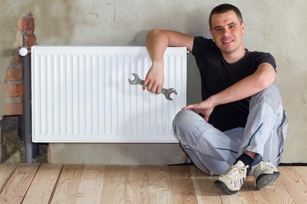Beau jeune plombier assis sur le sol avec une clé en main près d'un radiateur de chauffage installé avec succès dans une pièce vide d'un appartement ou d'une maison nouvellement construit. concept de construction, d'entretien et de réparation