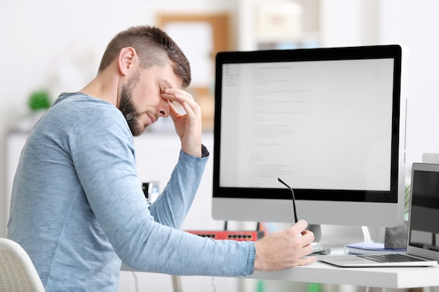 Beau jeune programmeur travaillant au bureau