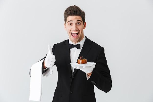 Beau jeune serveur en smoking avec noeud papillon tenant la plaque avec gâteau isolé sur mur blanc, pouces p