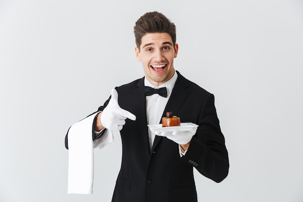 Beau jeune serveur en smoking avec noeud papillon tenant la plaque avec gâteau isolé sur mur blanc