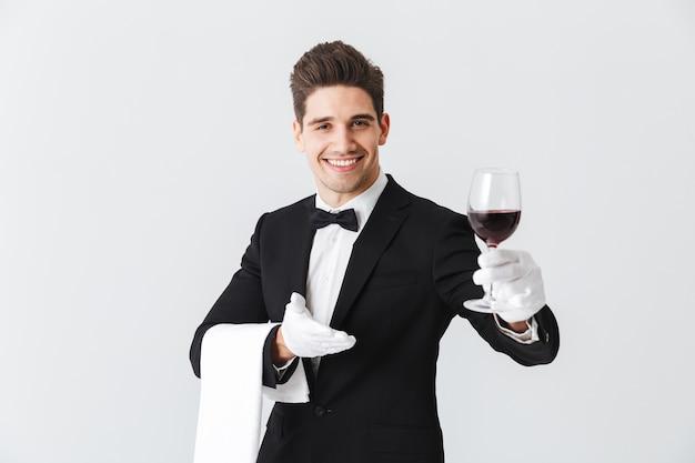 Beau jeune serveur en smoking tenant un verre de vin rouge isolé sur mur gris