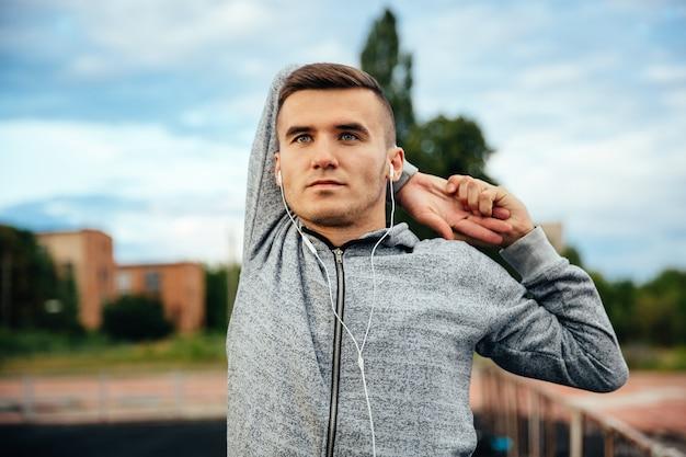 Beau jeune sportif confiant, faire des exercices pour les mains, tenant sa main