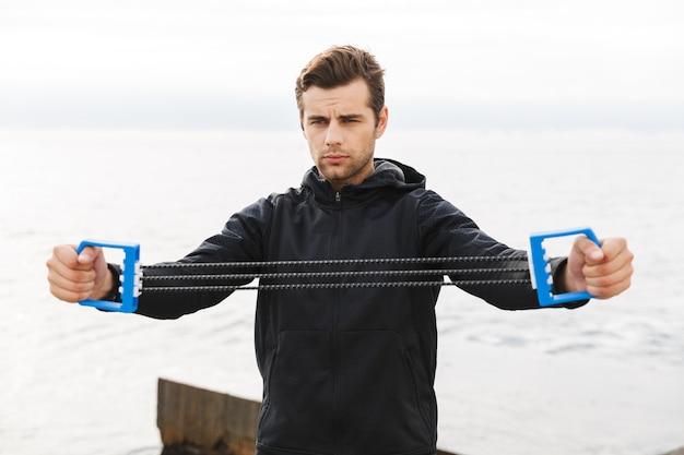 Beau jeune sportif confiant travaillant à la plage, à l'aide d'un extenseur de poitrine