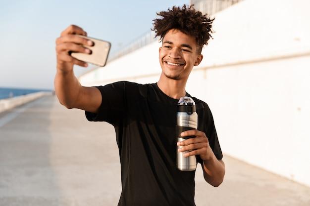 Beau jeune sportif debout à l'extérieur sur la plage faire selfie par téléphone avec de l'eau