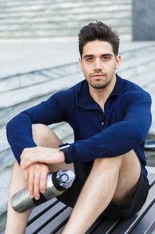 Beau jeune sportif de l'eau potable à partir d'une bouteille à l'extérieur, assis sur l'escalier