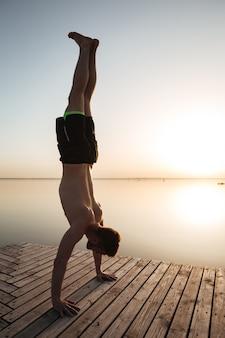 Beau jeune sportif fait des exercices de yoga à la plage.