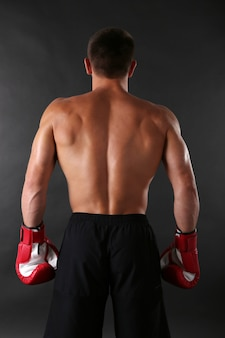 Beau jeune sportif musclé avec des gants de boxe sur une surface sombre