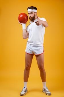 Beau jeune sportif sérieux tenant la balle faire les pouces vers le haut