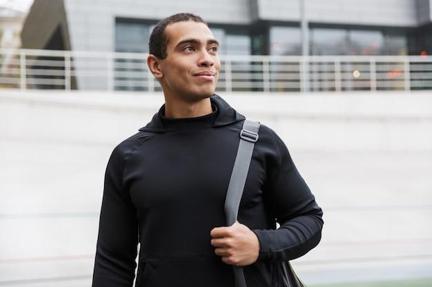 Beau jeune sportif souriant portant un sac de sport marchant à l'extérieur