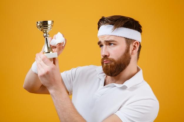 Beau jeune sportif tenant une récompense et essuyez avec une serviette