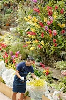Beau jeune travailleur de pépinière de fleurs asiatique souriant avec tablette numérique vérifiant les plantes et les fleurs emballées et préparées pour la livraison aux clients