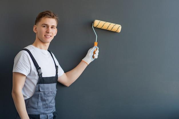 Beau jeune travailleur souriant avec rouleau à peinture sur fond gris
