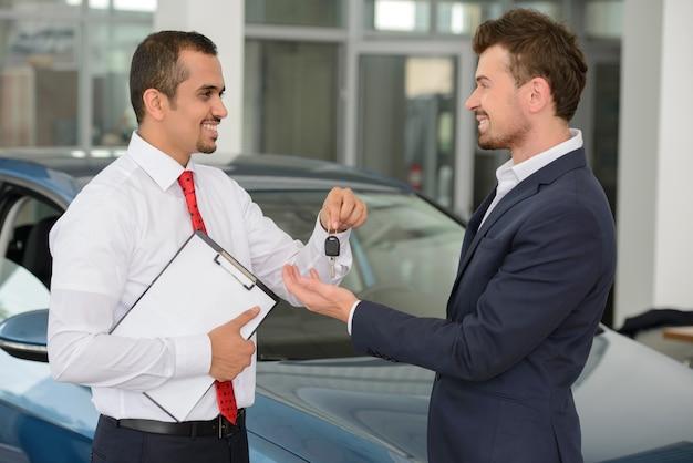 Beau jeune vendeur de voitures classiques donnant une clé de voiture.