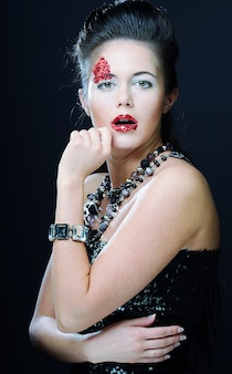 Beau jeune visage féminin avec le maquillage multicolore lumineux de mode